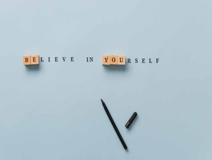 Believe in yourself sign spelled in combination of wooden blocks and letters on paper with emphasis on Be you message.